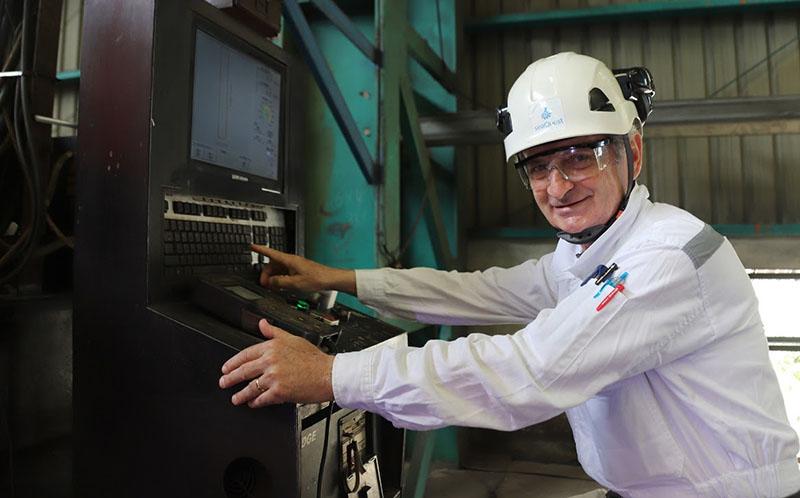 Un ingegnere aziona la macchina per il taglio della lamiera